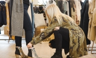 Angie Sunde, a stylist at leela & lavender, helps a woman try on a pair of boots.