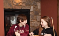 Riley and Brooke Cassibo play mancala in their fireside game room.