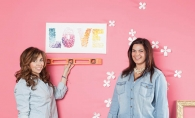 Erin Monasterio, left, and Becca Scott hang handmade ombre canvas art made of paint chip color samples in the shape of tiny butterflies.
