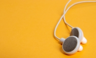 A pair of white headphones on a yellow background.
