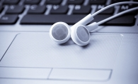 A pair of white headphones sit on a computer keyboard.