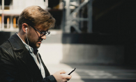 A man listens to trivia podcasts on his phone.