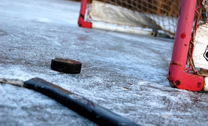 A hockey stick and puck rest in front of the net on an ice rink in Maple Grove.