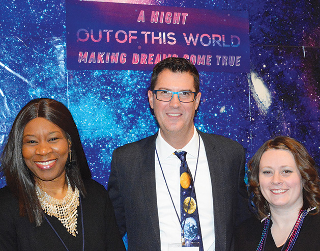 "Three people pose for a photo in front of a banner that reads ""A Night Out of This World, Making Dreams Come True"""