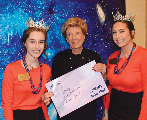 Two young women in tiaras pose with an older woman.
