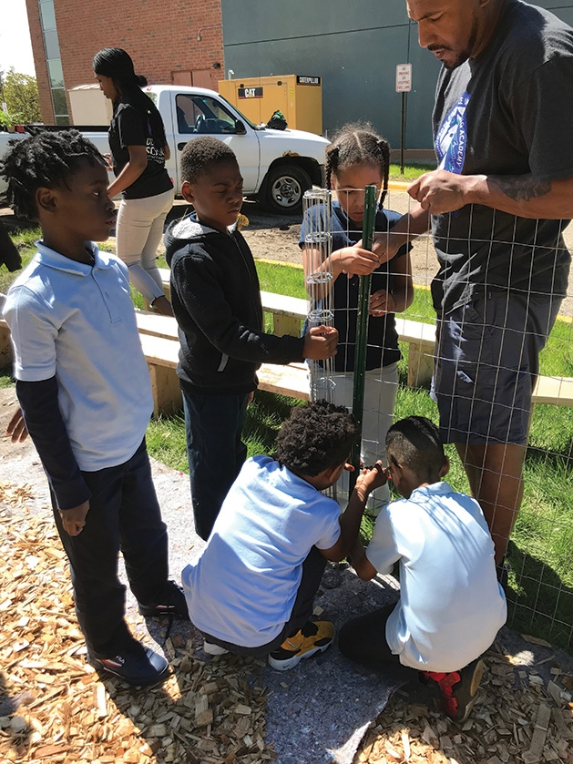 Minnesota Excellence in Learning Academy Students help put up a fence for the GROW garden.