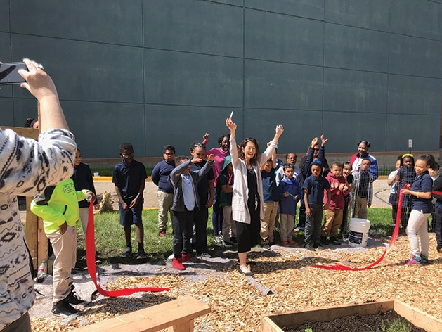 Minnesota Excellence in Learning Academy Principal Ms. Markworth celebrates after cutting a ribbon during the celebration with GROW.