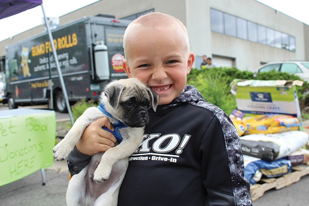 A child holds a puppy at the Feeding Furry Friends Family Fun Day.