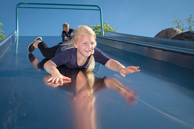 A girl slides down a slide at Central Park in Maple Grove.