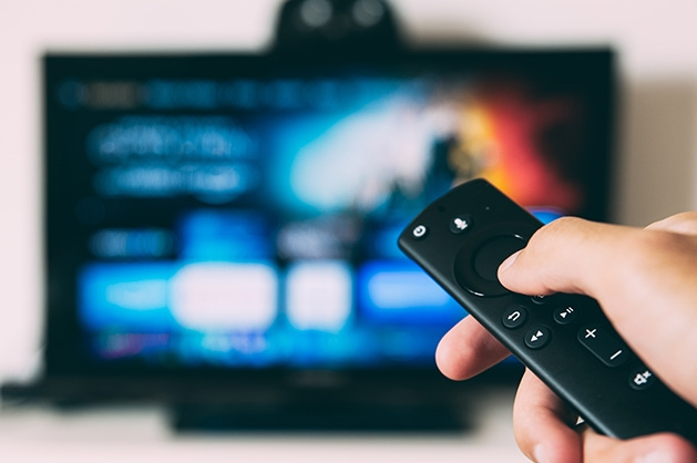 A person holds a remote while watching a streaming service.