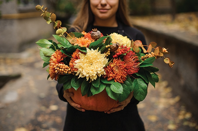 A woman holds a pumpkin full of flowers.