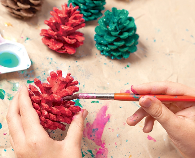 A person paints pinecones red and green.