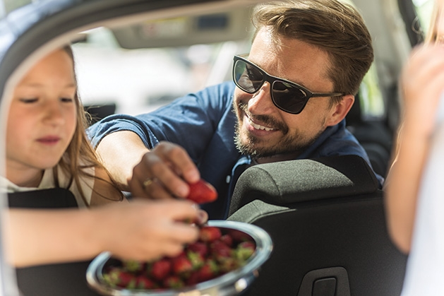 A family enjoys some strawberries during holiday travel.