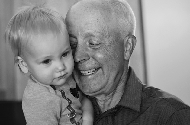 A grandfather holds his grandson in this Focus on Maple Grove winning photograph.