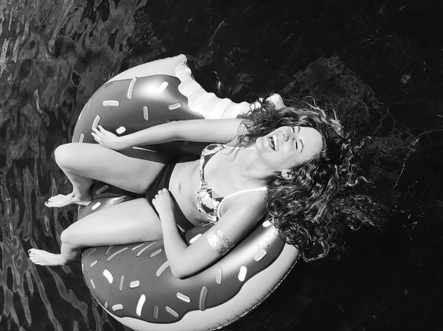 A woman lounges on an inflatable donut in a pool.