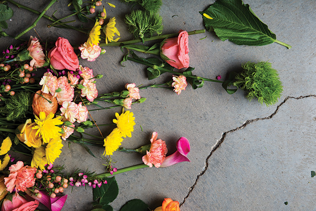 A variety of flowers rest on the concrete.