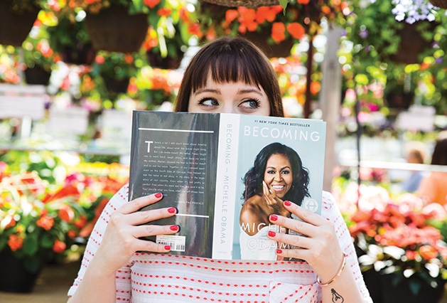 "A woman holds a copy of ""Becoming"" by Michelle Obama"