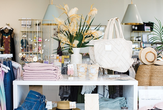 A display at Leela & Lavender at The Shoppes at Arbor Lakes includes sweaters, jeans, scarves, bags, candles and more.