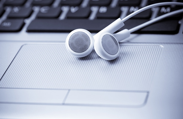 A pair of white headphones rest on a laptop.