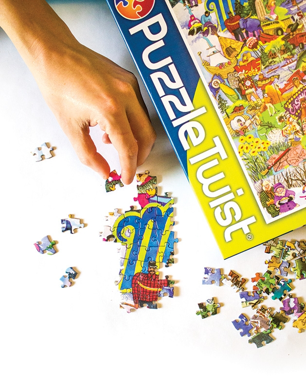A person places pieces in a puzzle.