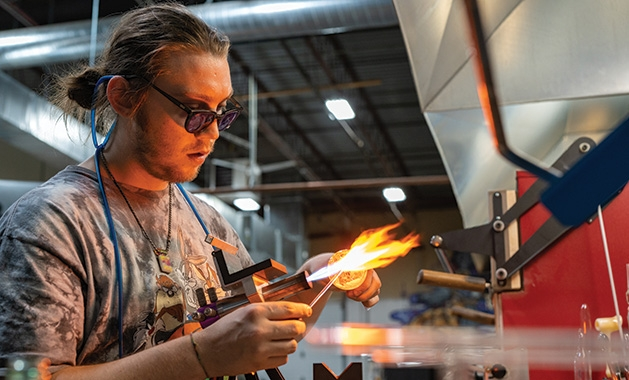A lampworking artist works the torch at Skylab Glass Arts