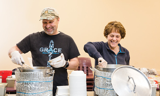 Richard and Carla Bahr, founders of nonprofit Threshold to New Life, serve food to people experiencing homelessness.