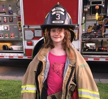 A girl at National Night Out in Maple Grove wears equipment from the Maple Grove Fire Department