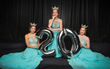 "Three Maple Grove ambassadors in blue dresses hold a silver ""20"" balloon."