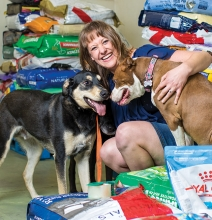 Amy Arellano, founder of pet food nonprofit Feeding Furry Friends, pets two of her dogs.