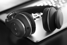 In this black and white photo, a pair of wireless headphones rests on a laptop.