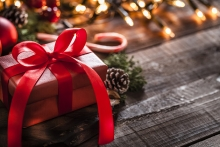 A wrapped Christmas present sits near a string of lights