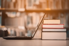 A laptop rests against some books at a library.