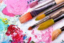 A set of paintbrushes sits on a colorful palate.
