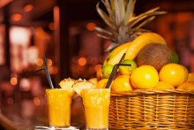 Two glasses of a summertime alcoholic punch rest on a bar in front of a basket of fresh fruit.