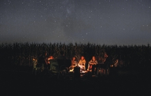 A group of kids sit around a campfire telling scary stories.