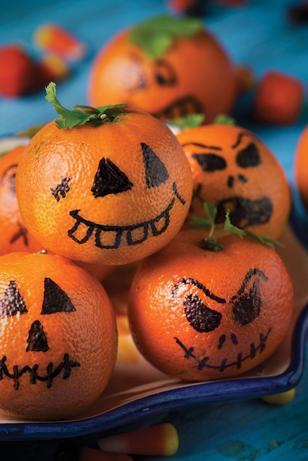Clementines with jack-o'-lantern faces drawn on,