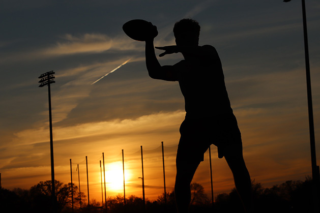 The silhouette of a boy playing football.
