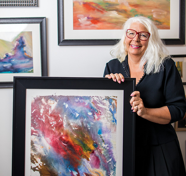 Watercolor artist CJ Longaecker poses with some of her paintings.