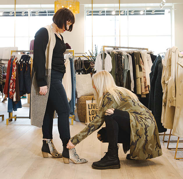 A stylist at leela & lavender helps a woman try on a pair of boots.