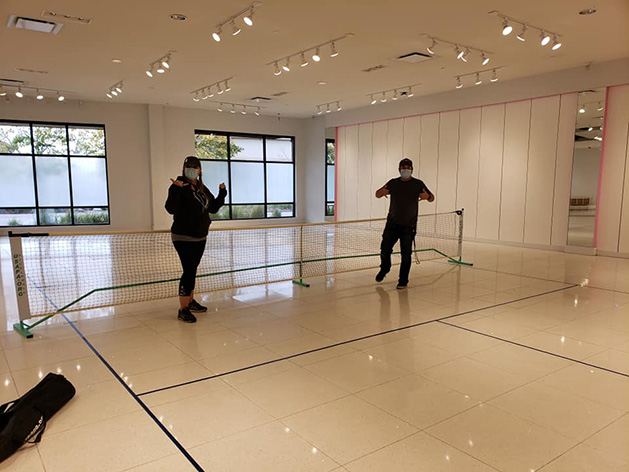 Two people on the pickleball courts at the new recreational space at The Shoppes at Arbor Lakes.