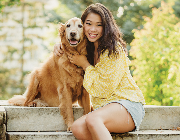A girl poses with her dog for a senior picture taken by Any Angle Photography